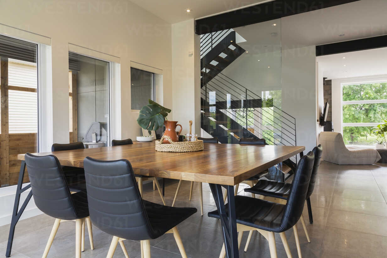 American walnut wood dining table and black leather sitting chairs ...