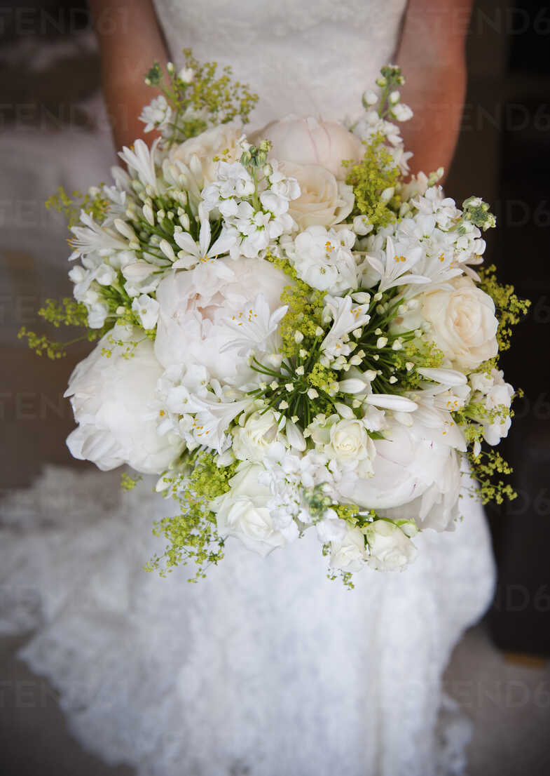 A woman in a white dress, a bride holding a bridal bouquet of ...