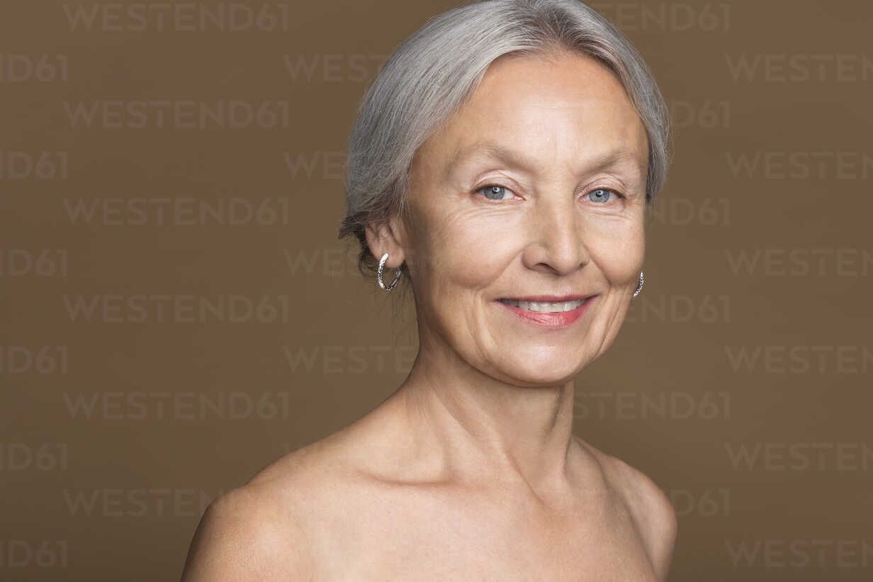 Mature woman nude portrait Portrait Of Naked Senior Woman In Front Of Brown Background Stockphoto