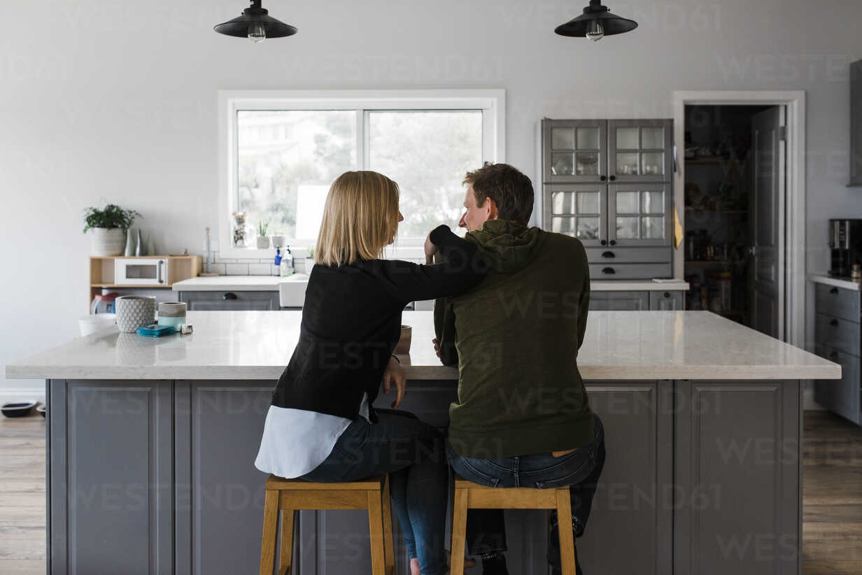 Rear view of couple sitting on stools in kitchen at home – Stockphoto