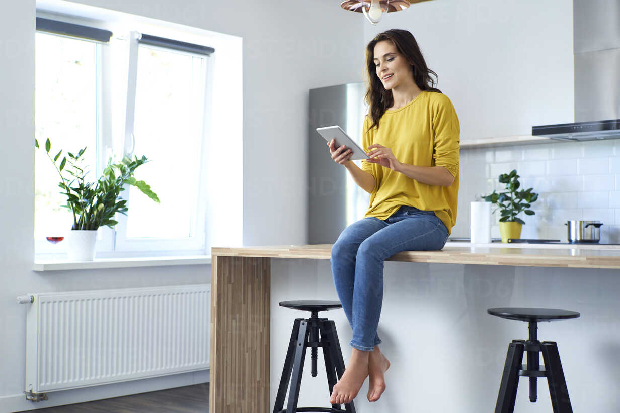 Woman sitting on kitchen counter at home, using digital tablet ...