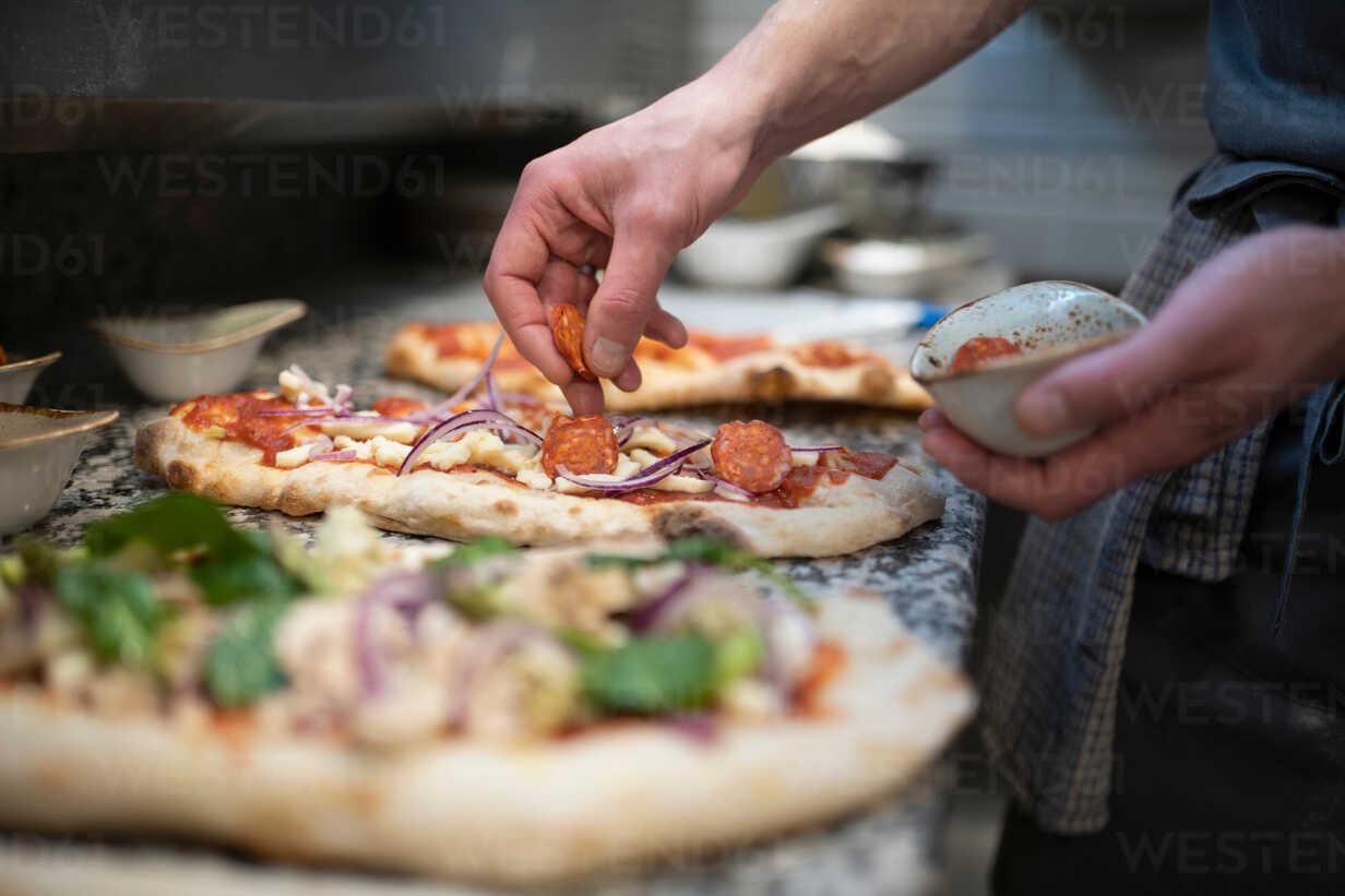 Chef placing sausage onto Pinsa Romana base, a Roman style pizza ...