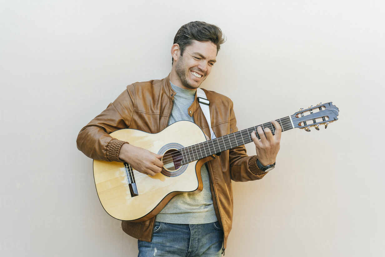 Smiling man playing guitar in front of a wall – Stockphoto