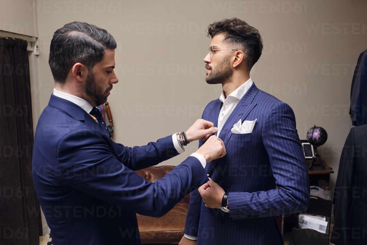 Tailor in his menswear store adjusting customers blue pinstripe ...